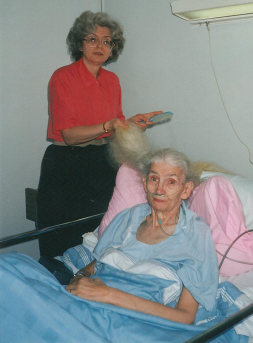 brushing Mom's hair in hospital bed